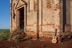 Den klassiska akustiska gitarren fördärvar in av övergiven kyrka Arkivbild