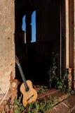 Den klassiska akustiska gitarren fördärvar in av övergiven kyrka Arkivbilder