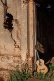 Den klassiska akustiska gitarren fördärvar in av övergiven kyrka Royaltyfri Foto