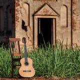 Den klassiska akustiska gitarren fördärvar in av övergiven kyrka Arkivfoto