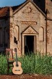Den klassiska akustiska gitarren fördärvar in av övergiven kyrka Royaltyfri Fotografi