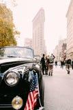 Den klassiska bilen för veterandag ståtar framme av strykjärnbyggnaden Arkivbild