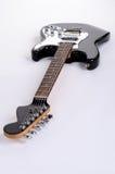 Den klassiska formen av den svartvita elektriska gitarren är den horisontellt framåt stämpeln med trälönnhalsen Royaltyfri Fotografi