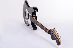 Den klassiska formen av den svartvita elektriska gitarren är en kant med trälönnhalsen Arkivbilder