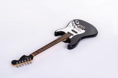 Den klassiska formen av den svartvita elektriska gitarren ligger horisontellt med trälönnhalsen Arkivfoton