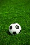 Den klassiska fotbollbollen som ligger i gräset, är det en solig dag i sommar arkivfoto