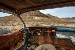 Den klassiska gamla bilen förfaller i en äng Arkivfoto