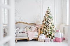 Den klassiska inre för julljus i vit och rosa färger tonar med en soffa, ett träd och en stöpning i den barocka stilen och Arkivfoto