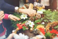 Den klippte sikten av dekoratören som skapar en julkrans av granfilialer, dekorativa bär, sörjer kottar och dekorativa leksaker i Arkivfoton