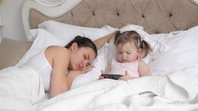 Den klyftiga lilla dottern använder mobiltelefonen, medan hennes trötta moder sover Härlig kvinna och gullig flicka med två stock video