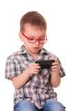 Den klyftiga ungen spelar med den smarta mobiltelefonen Royaltyfria Bilder