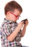 Den klyftiga ungen spelar med den smarta mobiltelefonen Arkivfoton