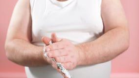 Den knubbiga mannen gnider hans händer som rakar skum som kontrollerar kvaliteten av produkten, ultrarapid arkivfilmer