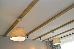 Den kombinerade belysningen - takljuskronor och lagt på lampor på trästrålarna som fixas på ett tak royaltyfri bild