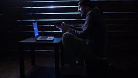 Den komiska roliga en hacker begår en cyberattack med en bärbar dator och ett vapen i hans händer stock video