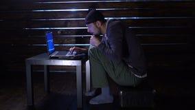 Den komiska roliga en hacker begår en cyberattack med en bärbar dator och ett vapen i hans händer arkivfilmer