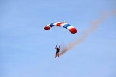 den kommande dykare jorda en kontakt ner parachutistskyen till Royaltyfri Foto