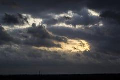 Den kommande solen ut bakifrån molnen Royaltyfri Fotografi