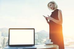 Den kompetenta affärskvinnan söker information på webbsidan via celltelefonen royaltyfria foton