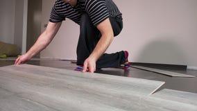 Den kompetenta byggmästaren som lägger trälaminaten, stiger ombord på golv arkivfilmer