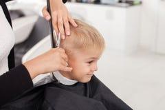 Den kompetenta unga kvinnliga frisören är den bitande människan arkivfoto