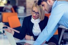 Den kompetenta yrkesmässiga blonda kvinnliga vd:n som förklarar till ung manlig anställd, kräver och strategi royaltyfria foton