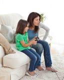 den koncentrerade dottern spelar den leka videoen för momen Arkivbild