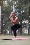 Den koncentrerade kvinnlign i yogaörn poserar i gräsplan parkerar royaltyfria bilder