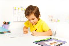Den koncentrerade lilla pojken skriver med den ensamma blyertspennan Royaltyfria Bilder