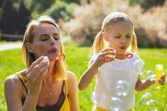 Den koncentrerade mamman som blåser bubblor, vissnar dottern arkivfoto