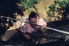 Den koncentrerade manklättraren klättrar en brant klippa Extremt begrepp för utomhus- aktivitet för livsstil arkivbild