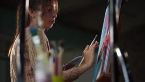 Den koncentrerade och inspirerade konstnären drar abstrakt plats på en linne på staffli lager videofilmer