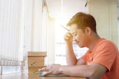 Den koncentrerade unga mannen läser en bok och att sitta på tabellen och wr royaltyfri fotografi