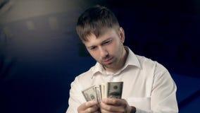 Den koncentrerade unga mannen räknar en bestämd mängd pengar för någon och når ut en hand med pengar lager videofilmer