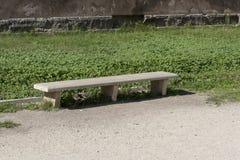 Den konkreta bänken i parkerar inget sitter arkivfoto