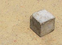 Den konkreta kuben som ligger på sandjordning som används av fattiga ungar för att spela som, leker med utrymme för meddelande el Arkivfoto