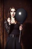 Den konstiga förskräckta flickan tränger igenom ballongen vid visaren Arkivfoto