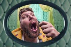 Den konstiga vuxna mannen drar ut hår från hans näsa Arkivbilder