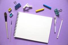 Den konstnärliga lägenheten lägger med vitboknotepaden, vattenfärgmålarfärger, borstar och pastell, det rosa färger tonade fotoet Fotografering för Bildbyråer