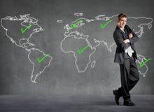 Den kontrollerade affärsmannen förlägger på en värld kartlägger royaltyfria bilder