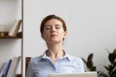 Den kopplade av affärskvinnan tar djup andedräkt av ny luft på arbetsplatsen arkivbilder