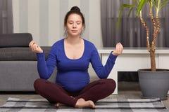 Den kopplade av bekymmerslösa gravida damen att sitta i lotusblomma poserar, övningsyoga hemma, leder sund livsstil, bär det blå  royaltyfri foto