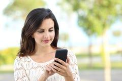 Den kopplade av damen som använder smartphonen i, parkerar royaltyfria bilder