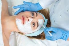 Den kopplade av unga kvinnan får ansikts- behandling för hudomsorg på skönhetsalongen Kosmetologen trycker på borsten med lera fö arkivfoto