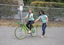 Den koreanska modern hjälper hennes åriga Amerasian dotterritt för tio en cykel i Seattle, Washington arkivfoto