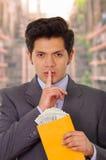 Den korrumperade politikern mottog pengar från en skurk inom av ett gult kuvert royaltyfria foton