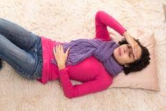 Den korta haired kvinnan känner sig att mycket smärtar och att ligga ner Royaltyfri Fotografi