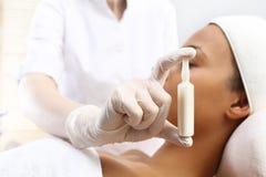 Den kosmetiska ampullen, serum applicerade till framsidan av en kvinna Royaltyfria Bilder