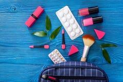 Den kosmetiska påsen med preventivmedel och preventivpillerar på blått bordlägger copyspace för den bästa sikten för bakgrund Arkivfoto