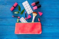 Den kosmetiska påsen med preventivmedel och preventivpillerar på blått bordlägger copyspace för den bästa sikten för bakgrund Royaltyfri Fotografi